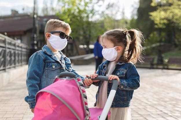 男の子と女の子は、保護マスクを乳母車と一緒に歩きます。家族の概念。コロナウイルス、covid-19