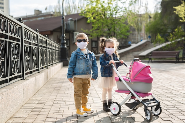 소년과 소녀는 보호용 안면 마스크를 쓴 유모차와 함께 걷습니다. 가족의 개념입니다. 코로나 바이러스 (코로나 19