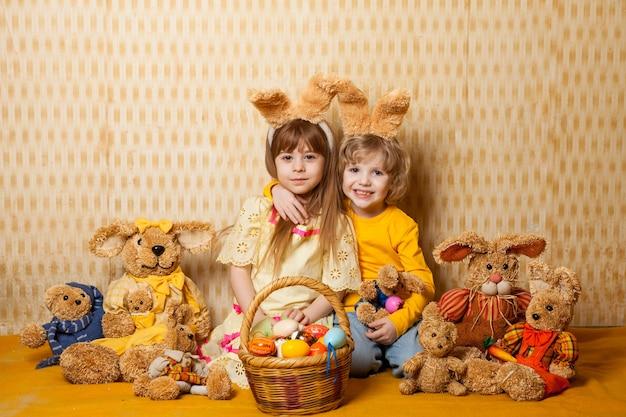 Мальчик и девочка с заячьими ушками и игрушками