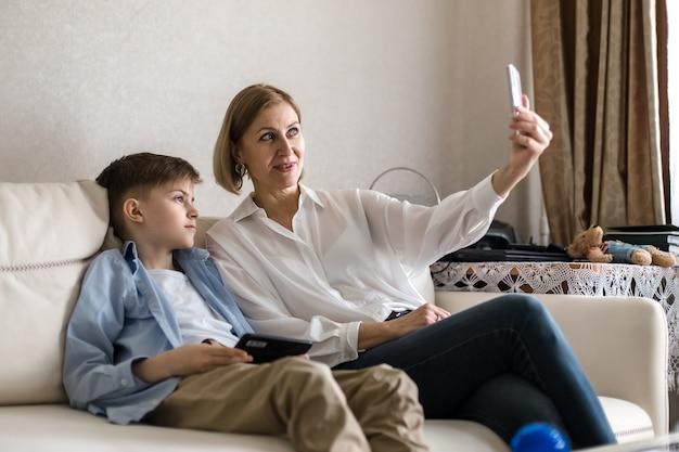 Мальчик и взрослая женщина делают селфи по телефону, сидя на диване