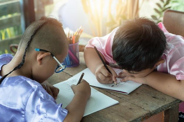 少年と友人は、絵を楽しく描いたり、絵を楽しんだり、家で本を書くつもりです。