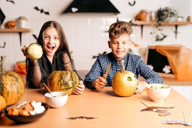 キッチンで家にいる男の子と女の子はカボチャの遊びと笑うハロウィーンのコンセプトで座っています