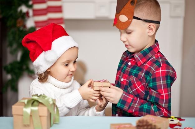 男の子と女の子の兄と妹はお互いにクリスマスプレゼントをします。