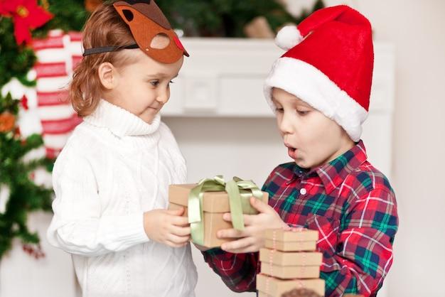 Мальчик и девочка, брат и сестра дарят друг другу рождественские подарки.