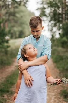 男の子と女の子、夏の自然の中で兄と妹を抱き締めて遊んでいます