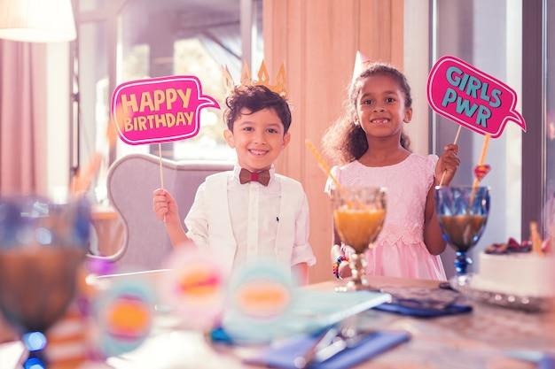 男の子と女の子。お誕生日おめでとうサインを保持し、フレンドリーな長い髪の女の子の近くに立っている間笑顔で陽気な面白い小さな男の子