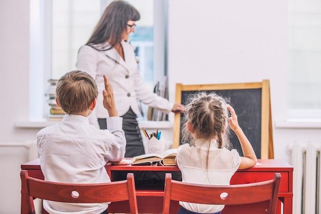 학교에서 선생님과 함께 소년과 소녀 아이들은 행복합니다. 교육, 지식의 날, 과학, 세대, 유치원, 교사의 날.