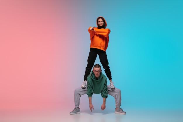 Мальчик и девочка танцуют хип-хоп в стильной одежде на градиентный фон в танцевальном зале в неоновом свете.