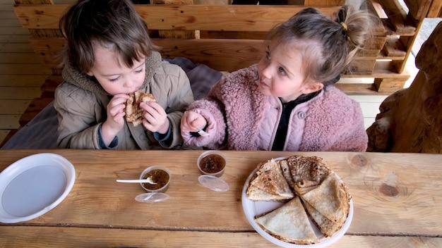 Мальчик и девочка едят вкусные свежие блинчики в уютном кафе
