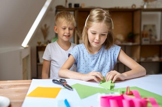 Мальчик и девочка клеят цветную бумагу, художественная школа
