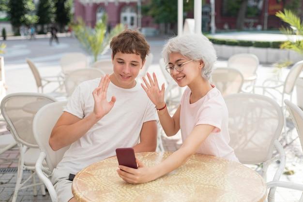 Мальчик и девочка с видеозвонком на улице