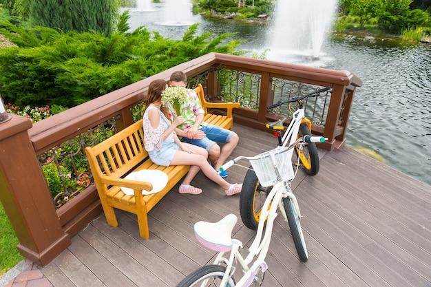 벤치에 앉아있는 동안 작은 흰색 꽃의 꽃다발 뒤에 숨어 키스하는 소년과 소녀는 공원에서 반대편에 자전거를 주차했습니다