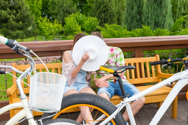벤치에 앉아 있는 동안 모자 뒤에 숨어서 키스하는 소년과 소녀는 공원에서 자신의 반대편에 자전거를 주차했습니다