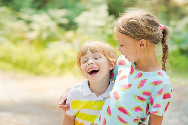 Мальчик и девочка смеются, обнимаются в парке. дружба, отношения, концепция любви