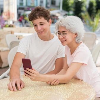 Мальчик и девочка, глядя на телефон снаружи