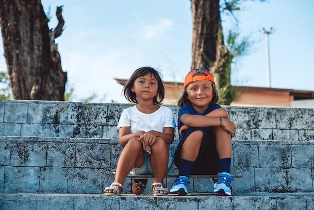 태국에서 휴가를 보내는 소년과 소녀. 그의 유치원 여동생과 스케이트보드에 앉아 야구 모자와 쾌활 한 어린 소년의 초상화.