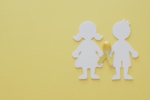 男の子と女の子の紙を黄色のゴールドリボンでカット、小児がんの意識