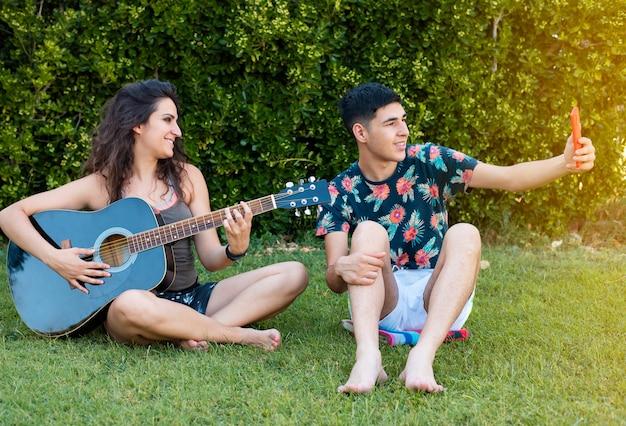 Мальчик и девочка играют на гитаре и поют в парке летом