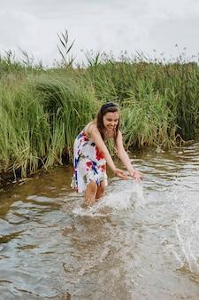 男の子と女の子が湖の岸に水で遊ぶ。夏休み。