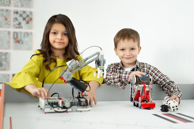 수제 로봇을 가지고 노는 소년과 소녀. diy 로봇 프로젝트, 재미와 개발, 방과 후 여가.