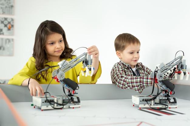 手作りロボットで遊ぶ男の子と女の子diyロボティクスプロジェクトの楽しさと開発