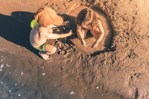 바다에서 모래를 가지고 노는 소년과 소녀. 상위 뷰, 복사 공간입니다.