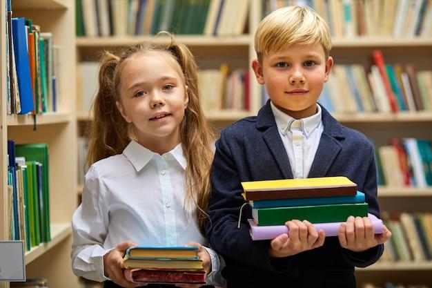 소년과 소녀는 학교를 준비하고, 그들은 학교 옷을 입고 카메라를보고 손에 책 더미를 들고 서 있습니다. 도서관에서