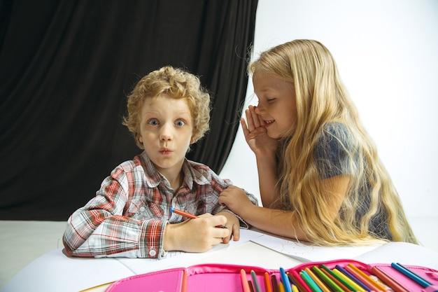 Мальчик и девочка готовятся к школе после долгих летних каникул.