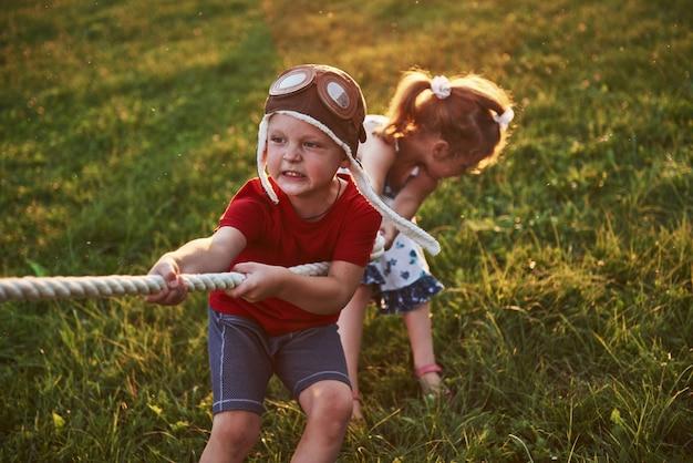 Мальчик и девочка, потянув веревку и играя перетягивание каната в парке
