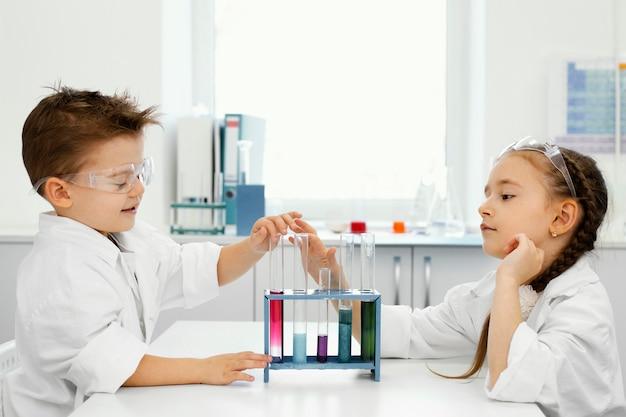 安全メガネと試験管を持った実験室の少年と少女の科学者