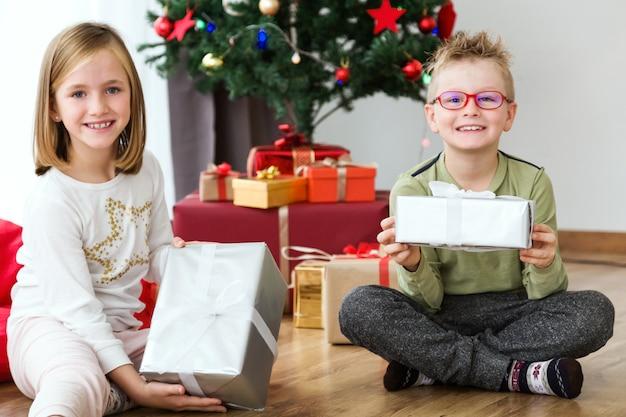 Мальчик и девочка, сидя на полу открытия подарок