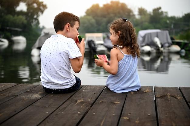 ボートを背景に日没時に桟橋に座って、スイカを食べる男の子と女の子。友情、優しさ、家族関係の概念。幸せな子供時代。