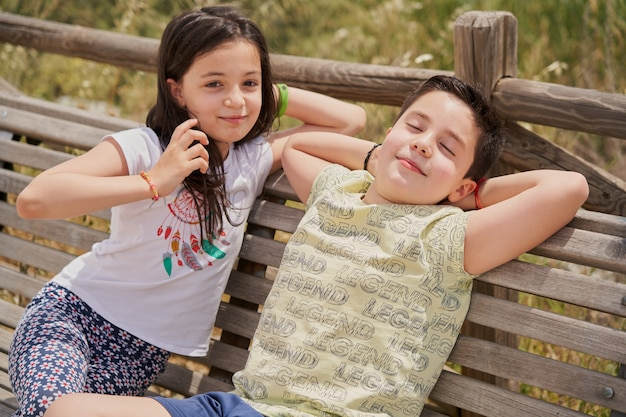 公園でリラックスして笑って木製のベンチに座っている男の子と女の子