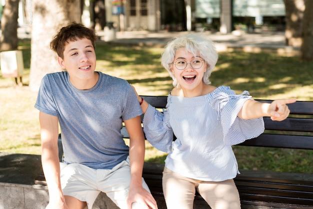 Мальчик и девочка сидят вместе на скамейке