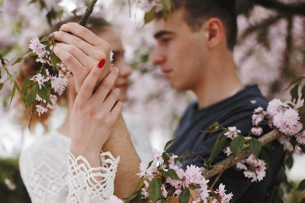 소년과 소녀는 꽃 봄 나무 아래 얼굴을 서