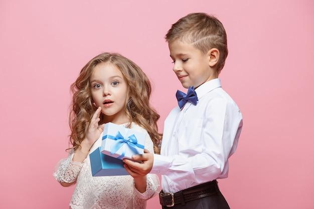 Мальчик и девочка стоя и позируют с подарком в студии на розовом фоне