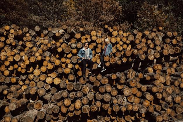 美しい色とりどりの秋の森の薪の山に立っている男の子と女の子。