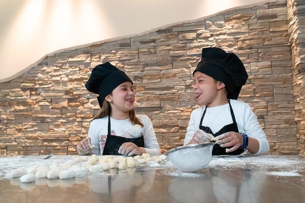 Мальчик и девочка высовывают языки во время кулинарного мастер-класса в костюмах поваров