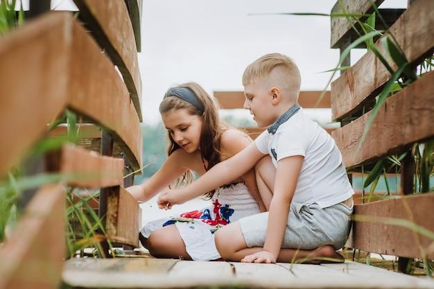Мальчик и девочка, шить на деревянном пирсе, летние каникулы