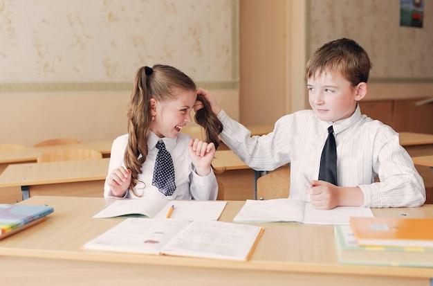Студенты-юноши и девушки с удовольствием сидят за партой. мальчик тянет девушку за косички.