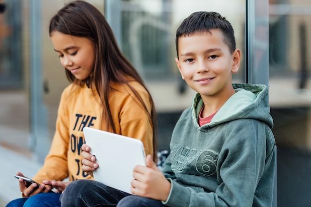 男の子と女の子は通りを歩いている間デジタルラップトップを使用し、週末の時間を過ごします。