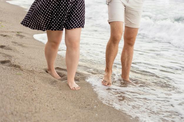 男の子と女の子がビーチの上を歩く