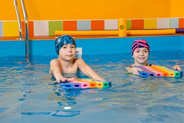 Мальчик и девочка в купальнике используют поролоновую подушку, чтобы поплавать в бассейне