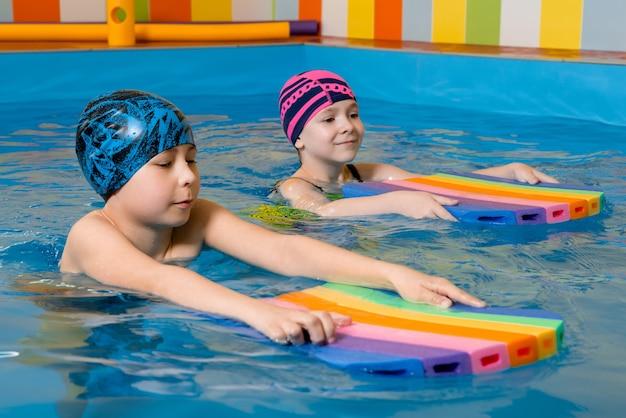 수영복을 입은 소년과 소녀는 거품 패드를 사용하여 수영장에서 수영을 연습합니다.