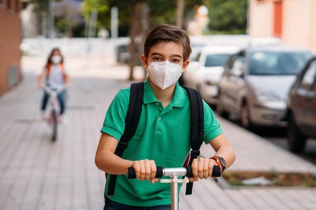Мальчик и девочка в масках и на скутере и велосипеде по улице