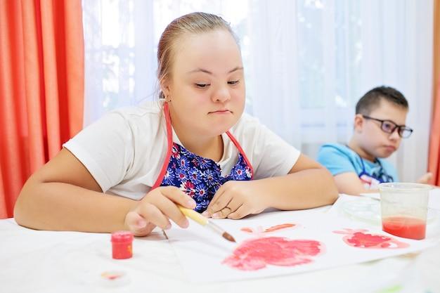ダウン症の男の子と女の子は、白い背景の上のテーブルに描画します。高品質の写真