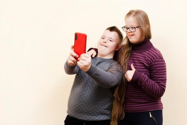 Мальчик и девочка с синдромом дауна, принимая селфи