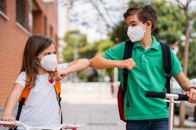 男の子と女の子の路上でマスク挨拶