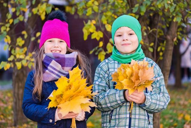 屋外で黄色の葉の花束を持つ少年と少女
