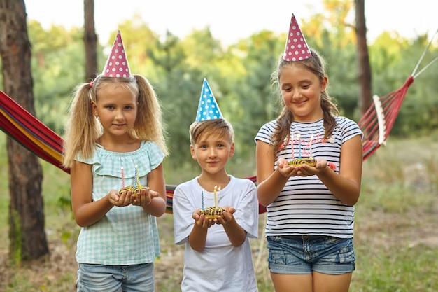정원에서 야외에서 생일을 축하하는 소년과 소녀